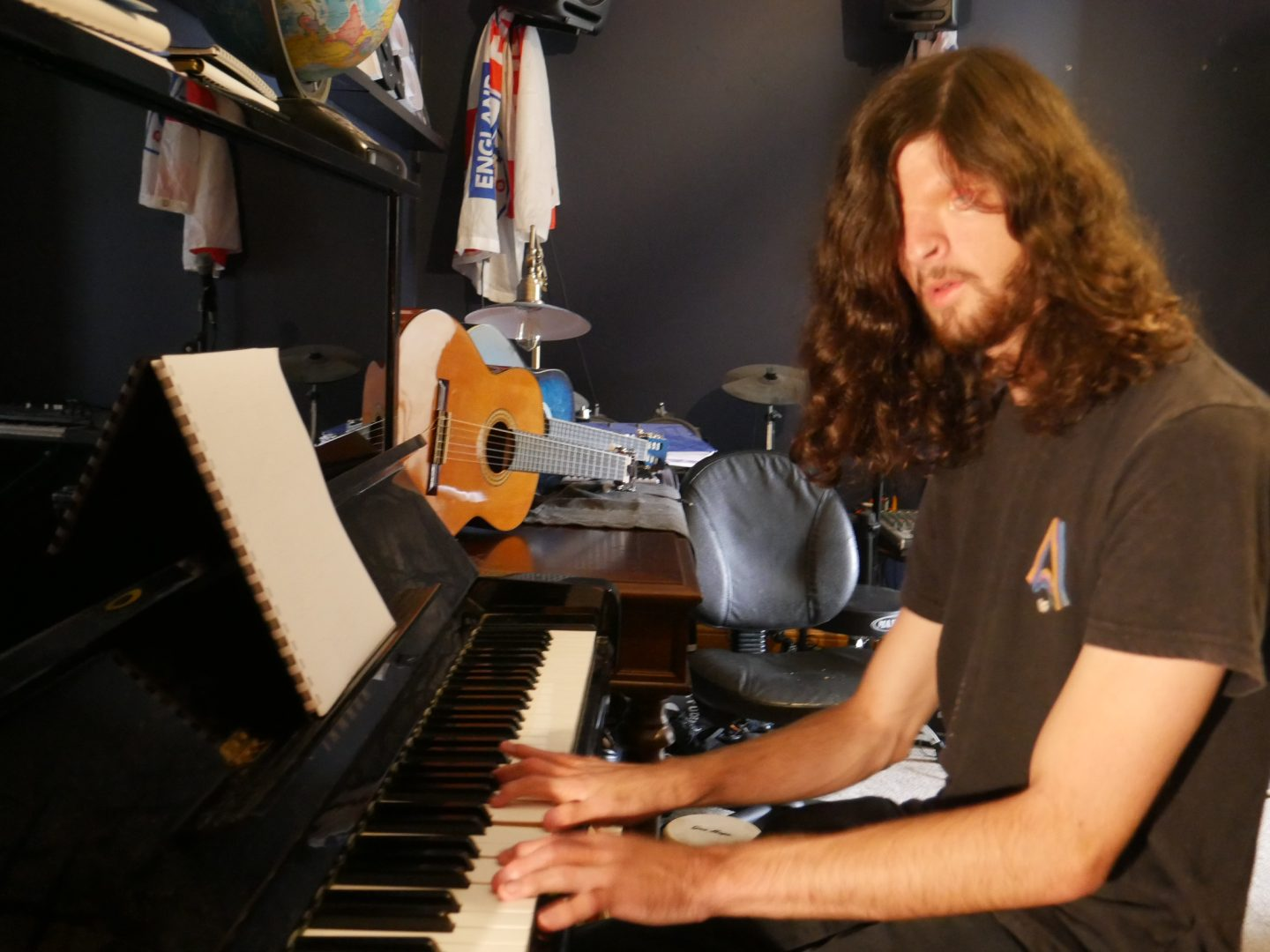 a man with long hair plays a piano