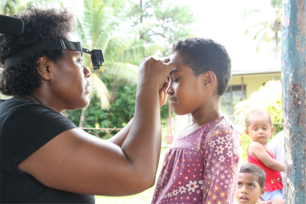 Dr vara screening an 8 year old for active trachoma.